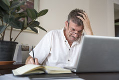 Middle aged man working at this computer at his home office Stock Photography