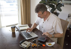 Middle aged man working at this computer at his home office Royalty Free Stock Image