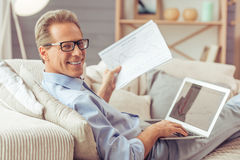 Middle aged man working. Handsome middle aged businessman in eyeglasses is using a laptop, looking at camera and smiling while working at home Royalty Free Stock Images