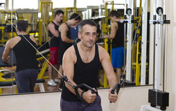 Middle aged man working out with gym equipment. Middle aged men working out with gym equipment, exercising pecs muscles with cables stock photo
