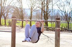 Middle-aged man working out on a horizontal bar. In an outdoor sports area in rural countryside in an active lifestyle and wellness concept Stock Photos