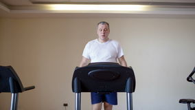Middle-aged man working out on a treadmill stock video