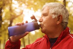Middle-aged man drinking water after workout. Middle-aged man workout in the park. Senior man drinking water after workout Royalty Free Stock Photos