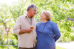 Middle aged married couple. Middle aged affectionate married couple in garden, men holding wine glass Stock Images
