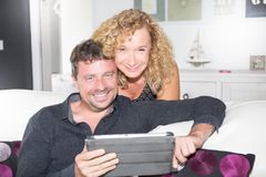 Middle aged married couple relaxing together at home surf internet on tablet. Happy middle aged married couple relaxing together at home surf internet on tablet Royalty Free Stock Photography