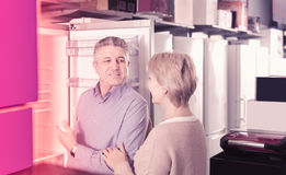 Middle-aged married couple in shop of household appliances are c Royalty Free Stock Photos