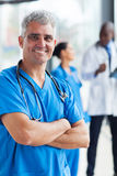 Middle aged medical doctor. Cheerful middle aged medical doctor with arms crossed in clinic Royalty Free Stock Photo
