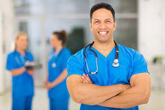 Middle aged medical doctor. Cheerful middle aged medical doctor with arms crossed in clinic Stock Photos