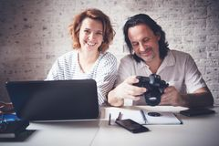 A middle-aged man and a young woman are sitting at a table with stock photos