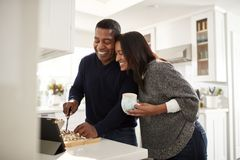 Middle aged African American  couple standing at worktop in the kitchen preparing food following a recipe on a tablet computer, se. Middle aged mixed race couple royalty free stock photography