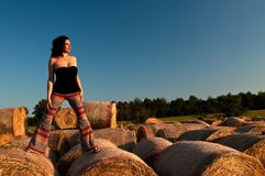Model on straw bales, Chianti, Tuscany. Middle aged model in black top and colorful slacks on hay bales in Chianti, Tuscany, Italy at sunset stock photo