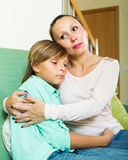Middle-aged mother comforting teenage boy. At home Royalty Free Stock Image