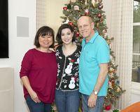 Middle-aged mother, elderly father and teenage daughter in front of a Christmas Tree stock photography