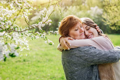 Middle-aged mother and her daughter hugging in blooming garden Royalty Free Stock Images