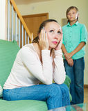 Middle-aged mother and teen  after quarrel at home. Focus on woman Royalty Free Stock Image