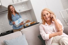 Mother and daughter together at home weekend woman talking on phone stock photography