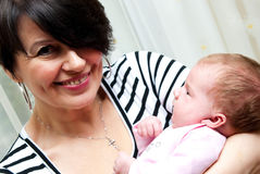 Middle aged mum with baby. Portrait of smiling middle aged mother or grandparent with baby girl Stock Photo