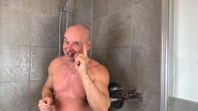 Middle-aged muscular bald man washes in the shower, laughs and threatens with a finger