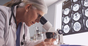 Middle aged neurologist female researching with microscope.  royalty free stock image