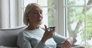 Older woman holding phone using virtual digital voice recognition