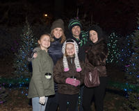 Middle-aged parents and three daughters outside standing in front of Christmas trees Royalty Free Stock Photo