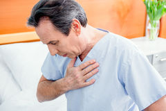 Middle aged patient with chest pain sitting on bed in chamber. In hospital Stock Image