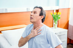 Middle aged patient with chest pain sitting on bed in chamber. In hospital Stock Photo