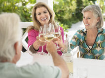 Middle Aged People Toasting Wine Glasses Outdoors. Three happy middle aged people toasting wine glasses at verandah table Royalty Free Stock Photos