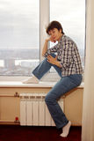 Middle aged pretty woman sits on a windowsill Royalty Free Stock Photography