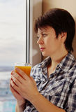 Middle aged pretty woman sitting on the windowsill with a glass of juice Royalty Free Stock Photo