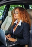 Middle-aged redhead businesswoman. Beautiful middle-aged redhead businesswoman in black jacket with laptop behind steering wheel Stock Image