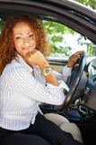 Middle-aged redhead woman in car. Beautiful smiling middle-aged redhead woman behind steering wheel Stock Photography