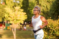 Middle aged 40s or 50s happy and attractive woman with grey hair training at city park with green trees on sunrise doing running. And jogging workout in health royalty free stock photos