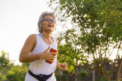 Middle aged 40s or 50s happy and attractive woman with grey hair training at city park with green trees on sunrise doing running. And jogging workout in health stock photo