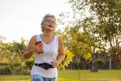 Middle aged 40s or 50s happy and attractive woman with grey hair training at city park with green trees on sunrise doing running. And jogging workout in health royalty free stock photo