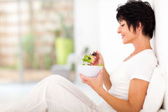 Middle aged salad. Elegant middle aged woman sitting on bed and eating salad Royalty Free Stock Photography