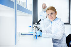 Middle aged scientist in protective eyewear working with microscope and colleague standing behind royalty free stock images