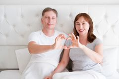 Middle aged senior couple in bed. Family happy relationship man and woman at bedroom interior. Sexual health and menopause period stock photos