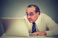 Middle aged shocked business man sitting in front of laptop computer looking at screen Royalty Free Stock Photo
