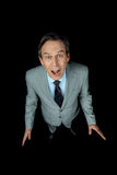 Middle aged shocked businessman in suit yelling on black. Overhead view of middle aged shocked businessman in suit yelling on black Royalty Free Stock Image