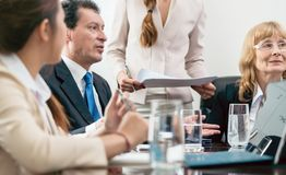 Middle-aged skilled manager cooperating with his colleagues royalty free stock photography