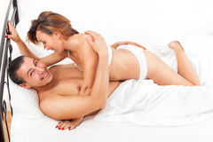 Middle-aged smiling couple kissing and playing on white sheet in Stock Images
