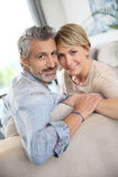 Middle-aged smiling couple on sofa. Middle-aged couple relaxing in sofa at home Royalty Free Stock Photo
