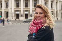 Middle-aged smiling happy woman with blond hair. Wearing pink scarf and black jacket while standing in front of historic building Stock Images