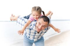 Middle-aged smiling man playing with a little girl Stock Photo