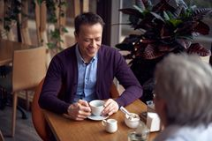 Middle aged smiling man sitting in cafe. Enjoyable meetings. Waist up top angle portrait of middle aged casual style handsome male sitting in cafe and drinking royalty free stock image