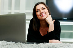 Middle-aged smiling woman lying on the carpet with laptop Stock Photography