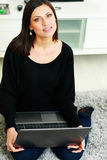 Middle-aged smiling woman sitting on the floor with laptop Royalty Free Stock Photos