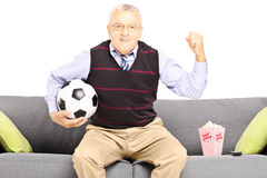Middle aged sport fan holding a soccer ball and watching sport. Isolated on white background Royalty Free Stock Image