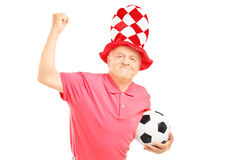 Middle Aged Sport Fan With Hat Holding A Soccer Ball And Gesturi Royalty Free Stock Image